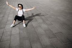 La muchacha feliz de moda del inconformista con el sombrero y las gafas de sol se divierten que se sienta en el piso Copie el áre Foto de archivo libre de regalías