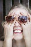 La muchacha feliz, de risa cubrió su cara por las manos, llevando sunglass Imagen de archivo