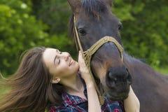 La muchacha feliz del adolescente abraza su caballo Fotografía de archivo libre de regalías