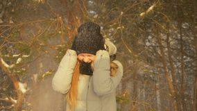 La muchacha feliz del adolescente disfruta de las nevadas en día soleado y cubierta del bosque del árbol de pino del invierno con metrajes