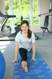 La muchacha feliz del adolescente en la estera en gimnasio hace fractura Imagen de archivo libre de regalías
