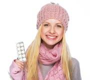 La muchacha feliz del adolescente en sombrero del invierno y la bufanda que muestra píldoras embalan Fotos de archivo libres de regalías
