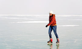 La muchacha feliz del adolescente está patinando en el lago congelado Bala Foto de archivo