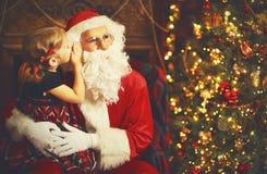 La muchacha feliz del niño abraza a Santa Claus, y le dice secreto foto de archivo libre de regalías