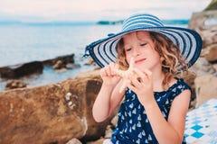 La muchacha feliz del niño en el sombrero de la raya que juega en la playa y escucha la cáscara del mar foto de archivo
