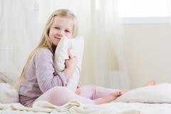 La muchacha feliz del niño está sosteniendo la almohada en cama Imagen de archivo libre de regalías