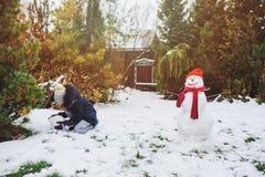la muchacha feliz del niño que hace al hombre de la nieve en la Navidad vacations en patio trasero fotografía de archivo libre de regalías