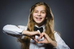 La muchacha feliz del retrato del primer muestra las manos en la forma del corazón fotos de archivo