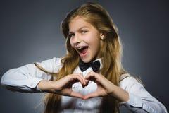La muchacha feliz del retrato del primer muestra las manos en la forma del corazón imagenes de archivo