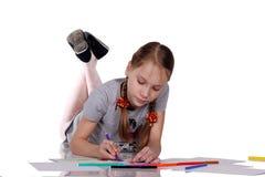 La muchacha feliz dibuja y escribe imagenes de archivo