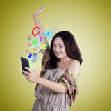 La muchacha feliz disfruta de Internet en el teléfono móvil Foto de archivo