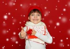La muchacha feliz en el sombrero de santa con lanas del árbol de abeto de la demostración del regalo de la caja juega en el rojo  Fotos de archivo