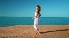 La muchacha feliz en el vestido blanco corre al mar y disfruta almacen de video