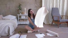 La muchacha feliz en guardapolvos de los vaqueros es visión en el papel pintado para renovar el interior casero entonces que mir metrajes