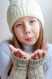 La muchacha feliz en invierno viste soplar en la felicidad a del invierno de las palmas Imagen de archivo libre de regalías