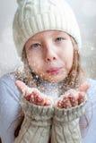 La muchacha feliz en invierno viste soplar en la felicidad a del invierno de las palmas Fotos de archivo