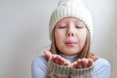 La muchacha feliz en invierno viste soplar en la felicidad a del invierno de las palmas Fotografía de archivo