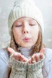 La muchacha feliz en invierno viste soplar en la felicidad a del invierno de las palmas Imágenes de archivo libres de regalías