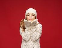 La muchacha feliz en invierno viste soplar en las palmas Foto de archivo