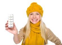 La muchacha feliz en la ropa del otoño que muestra píldoras embala Imagen de archivo libre de regalías