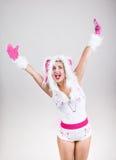 La muchacha feliz en la sensación del traje del conejo excitó el aumento de sus manos para arriba Foto de archivo