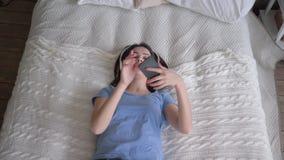 La muchacha feliz en los auriculares se cae en cama y escucha las canciones de la música del smartphone y del condimento mientra metrajes