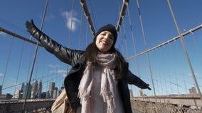 La muchacha feliz en Nueva York goza del puente de Brooklyn hermoso almacen de metraje de vídeo