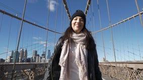 La muchacha feliz en Nueva York goza del puente de Brooklyn hermoso metrajes