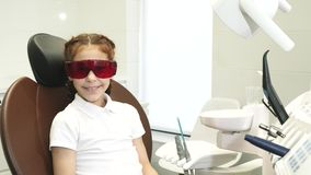 La muchacha feliz en la recepción en el dentista muestra los pulgares para arriba metrajes