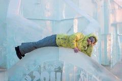 La muchacha feliz en ropa caliente amarilla miente en escultura de hielo fotos de archivo