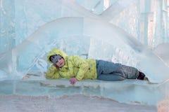 La muchacha feliz en ropa caliente amarilla miente en escultura de hielo en el winte fotos de archivo libres de regalías