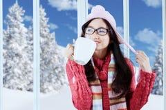 La muchacha feliz en ropa del invierno disfruta de la bebida caliente Imagen de archivo libre de regalías