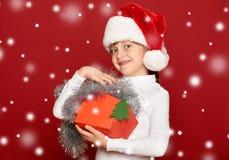 La muchacha feliz en sombrero con lanas del árbol de abeto de la demostración del regalo de la caja juega en fondo rojo Fotos de archivo