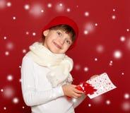 La muchacha feliz en sombrero con lanas del árbol de abeto de la demostración del regalo de la caja juega en rojo Imagenes de archivo