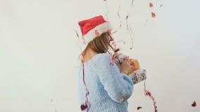 La muchacha feliz en sombrero del ` s de santa con los regalos disfruta el confeti en un fondo blanco almacen de metraje de vídeo