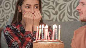 La muchacha feliz en su cumpleaños hace un deseo y sopla hacia fuera las velas en la torta fotos de archivo libres de regalías