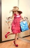 La muchacha feliz en talones y un sombrero con el regalo empaquetan Imágenes de archivo libres de regalías