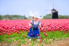 La muchacha feliz en traje holandés en tulipanes coloca con el molino de viento Fotos de archivo libres de regalías