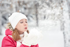La muchacha feliz en un paseo escarchado del invierno en la calle sopla nieve de las manos Fotografía de archivo