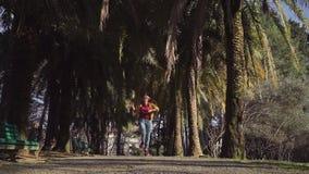 La muchacha feliz en vaqueros y una chaqueta amarilla corre abajo del callejón con las palmeras y salta a veces para arriba y las metrajes