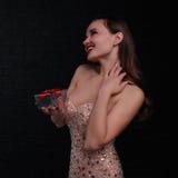La muchacha feliz en vestido rosado sostiene una caja de regalo Fotografía de archivo