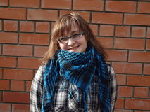 La muchacha feliz en vidrios y chaqueta de la tela escocesa y la bufanda permanecen sobre bric Fotografía de archivo