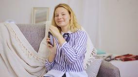 La muchacha feliz escribe mensajes en smartphone almacen de video