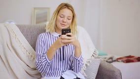 La muchacha feliz escribe mensajes en smartphone almacen de metraje de vídeo