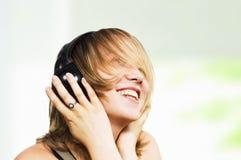La muchacha feliz escucha la música Imagen de archivo libre de regalías