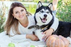 La muchacha feliz está abrazando su perro fornido al aire libre Fotografía de archivo