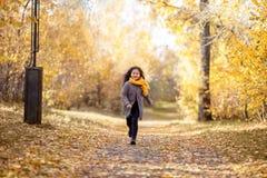 La muchacha feliz está corriendo en parque del otoño imagenes de archivo