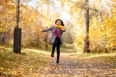La muchacha feliz está corriendo en parque del otoño imagen de archivo
