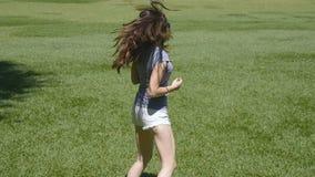 La muchacha feliz está corriendo a lo largo de hierba verde en el campo y está aumentando las manos Mujer hermosa joven que activ almacen de video