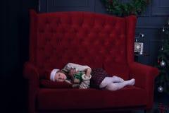 La muchacha feliz está durmiendo dulce cerca de un árbol de navidad Fotografía de archivo libre de regalías